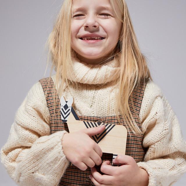 Dziewczynka przytulająca drewnianą zabawkę - zebrę. Projekt Dzioopla