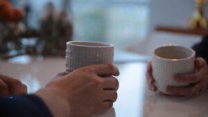 Dłonie trzymające kubki ceramiczne podczas rozmowy 2 osób przy stoliku. Słuchające kubki. Proj. Audrey Desjardins, Timea Tihanyi.