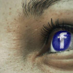 Zbliżenie twarzy z logo Facebook w tęczówce oka